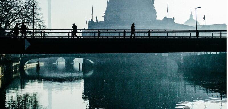 Fußgänger im Nebel laufen über Brücke am Berliner Bodemuseum