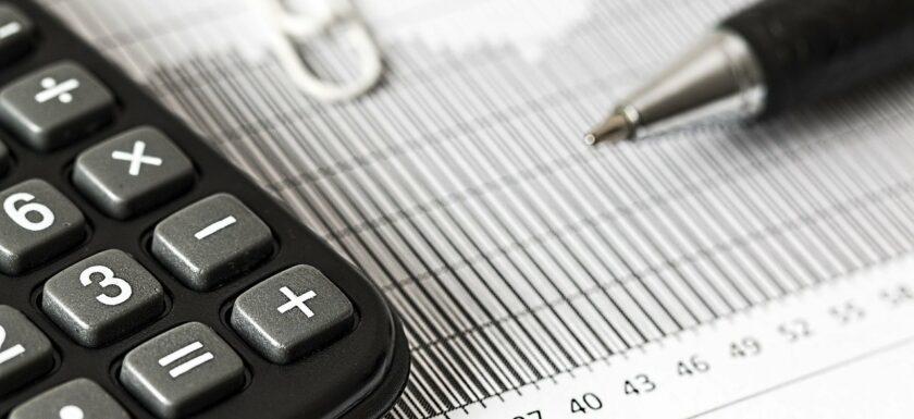 Taschenrechner und Stift zur Ermittlung des Unternehmenswertes bei Erbschaft
